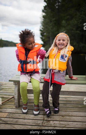 Sweden, Medelpad, Two girls (6-7) wearing life jackets - Stock Photo