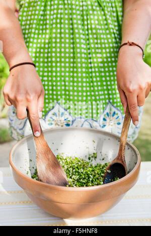 Sweden, Skane, Hoganas, Woman preparing salad in bowl - Stock Photo