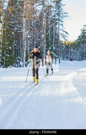 Sweden, Couple skiing in forest - Stock Photo