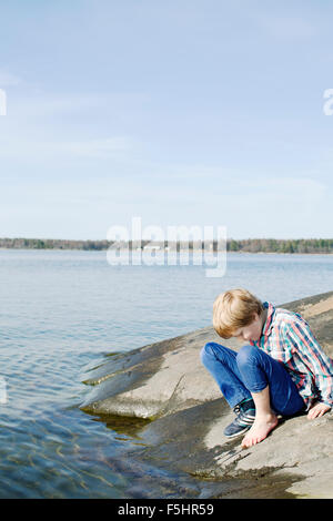 Sweden, Uppland, Oregrund, Boy (8-9) checking temperature of sea water with his foot - Stock Photo