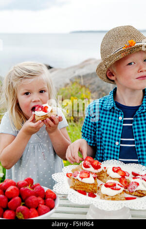 Sweden, Uppland, Roslagen, Children (6-7, 8-9) eating strawberry dessert outdoors - Stock Photo