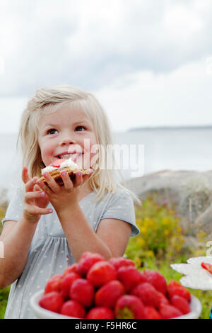 Sweden, Uppland, Roslagen, Girl (6-7) eating strawberry dessert outdoors - Stock Photo