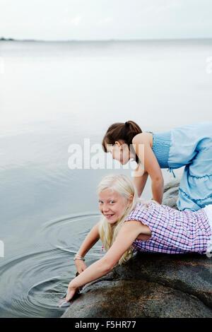 Sweden, Uppland, Roslagen, Two girls (12-13) playing at seaside - Stock Photo
