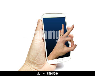 Hand holding smart phone with hand making international ok sign coming out of screen - Stock Photo