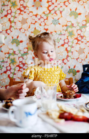 Sweden, Boy (10-11) and girl (2-3) eating cake - Stock Photo