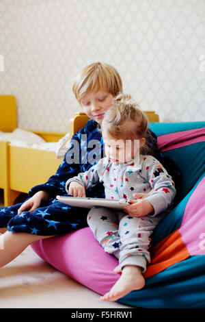 Sweden, Boy (10-11) and girl (2-3) using tablet - Stock Photo