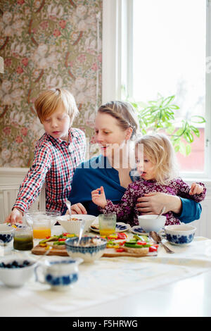 Sweden, Mother with two children (2-3, 10-11) eating breakfast - Stock Photo