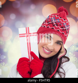 Composite image of festive brunette in winter clothes pointing gift - Stock Photo
