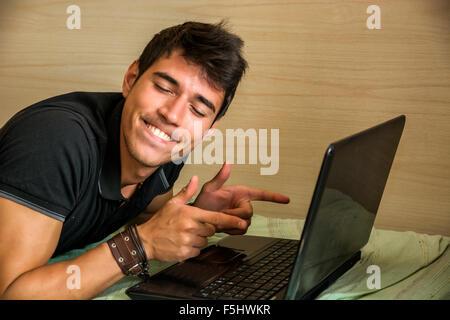Young handsome man pointing gun, wearing black t-shirt ...
