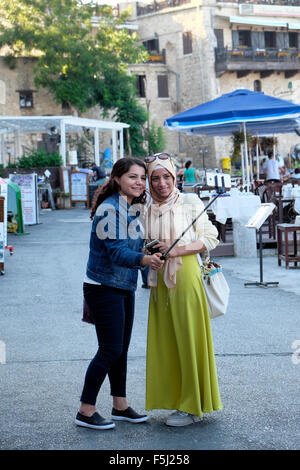 Young Muslim women friends taking a selfie photograph along the harbour front in Kyrenia Girne North Cyprus  KATHY - Stock Photo