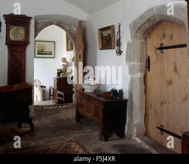Antique long-case clock and wooden chest in a hall with a wooden door in a large country house in South Wales - Stock Photo