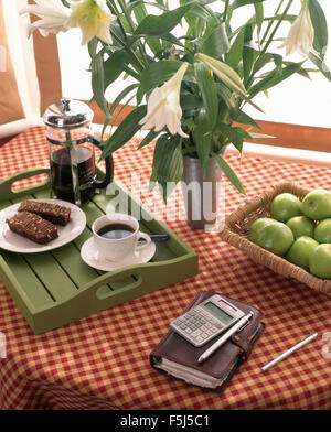 Vase of white lilies and Filofax with a calculator on a table with a cafetiere and cup of coffee on a green tray