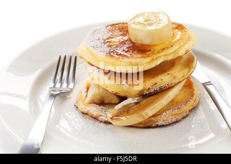 fluffy ricotta pancakes with banana isolated on white background - Stock Photo