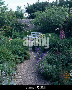 Pink foxgloves and blue perennial geraniums in border beside gravel path to terrace with a white bench in walled - Stock Photo