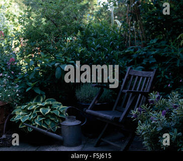 Old galvanized zinc watering can and a wooden lounger chair on a shady patio with a variegated hosta - Stock Photo