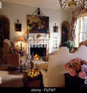 Painting above fireplace with lighted fire in opulent eighties living room with a wing chair and a cream camel back - Stock Photo