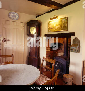 Antique long case clock in corner of traditional an eighties cottage dining room with a wood burning stove in a - Stock Photo