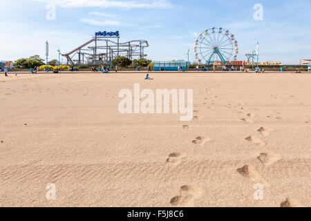 Footprints on the beach leading to the Pleasure Beach fairground at Skegness, Lincolnshire, England, UK - Stock Photo