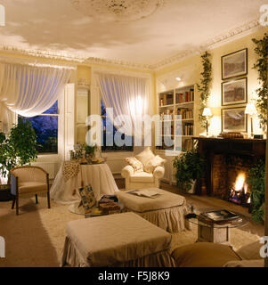White voile drapes on windows in eighties apartment living room with lighted fire in fireplace - Stock Photo
