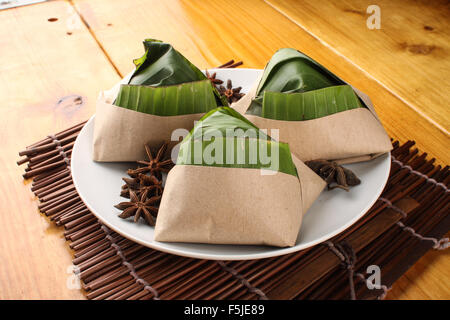traditional fresh Malaysian nasi lemak packed with banana leaf in wood background - Stock Photo