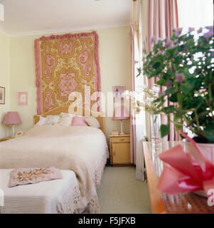 Patterned pink wool rug on wall above the bed in eighties bedroom - Stock Photo