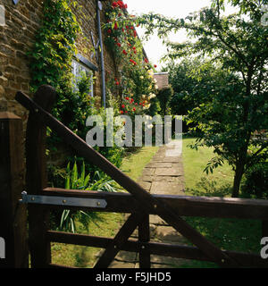 View across five bar wooden gate of path to country house with roses on the walls - Stock Photo