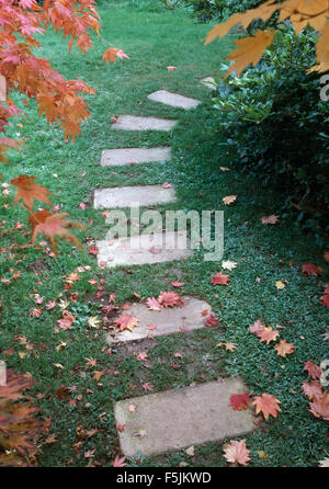 Close-up of stone paving slabs across a lawn in an Autumn garden - Stock Photo