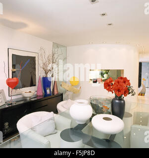 White ceramic vases and a vase of red amaryllis on a glass topped table with white tub chairs in a nineties dining - Stock Photo