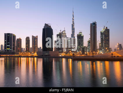 Skyline of towers reflected in the Creek at dusk in Business Bay  in Dubai United Arab Emirates - Stock Photo