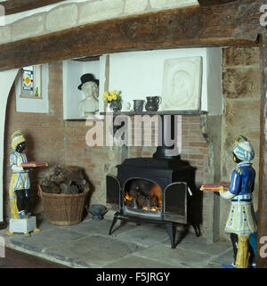 Blackamoor china figures either side of a wood burning stove in an inglenook fireplace - Stock Photo