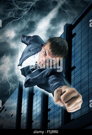 Superhero businessman flying over downtown in thunderstorm - Stock Photo