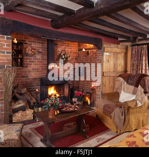 Wood burning stove in inglenook fireplace in  a beamed nineties country living room with an oak coffee table beside - Stock Photo