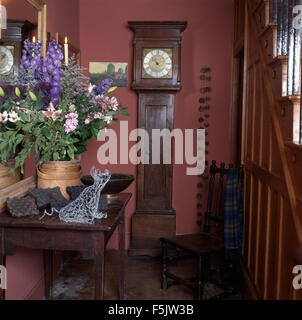 Summer flower arrangement on console table in a nineties pink cottage hall with an antique long case clock and wooden - Stock Photo