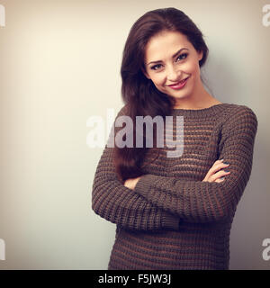 Happy young brunette woman smiling in warm sweater. Vintage portrait - Stock Photo