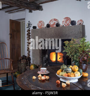 Bowl of gourds on table in country dining room with a wood burning stove in stone fireplace - Stock Photo