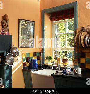Blue jug beside Belfast sink below window in a small nineties pale terracotta painted country kitchen - Stock Photo