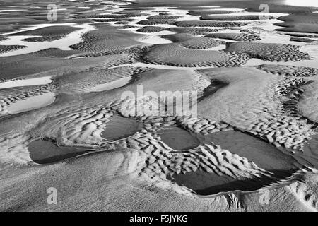 Sand ripples and pools on the beach filled with sea water at low tide. Black and white - Stock Photo