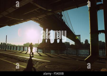 A runner jogs up the East River Esplanade under Manhattan Bridge as the sun rises - Stock Photo