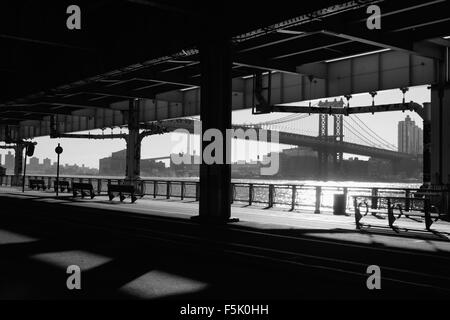 A view of the East River Esplanade, New York, under the Franklin D. Roosevelt East River Drive overpass as the sun - Stock Photo