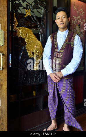 Burmese waiter on RV Paukan Ayeyarwaddy River cruise waiting by  the ornate traditionally carved  dinning room entrance - Stock Photo