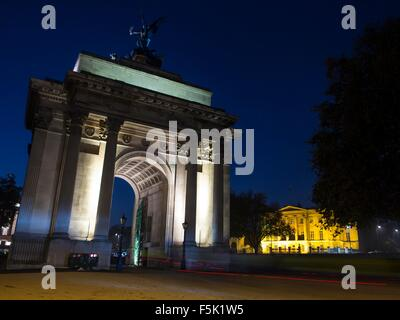 Cyclists riding through Wellington Arch at Hyde Park Corner in London at night - Stock Photo