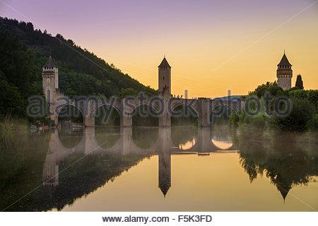 Evening dusk over Pont Valentre along River Lot at Cahors, Midi-Pyrenees, Occitanie, France - Stock Photo