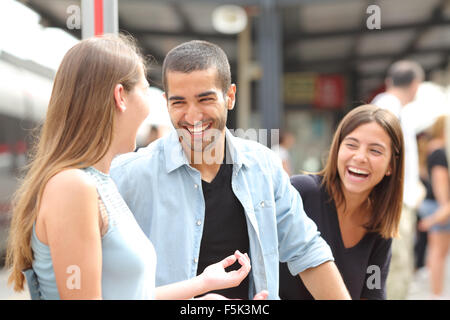 Three friends talking and laughing taking a conversation in a train station - Stock Photo
