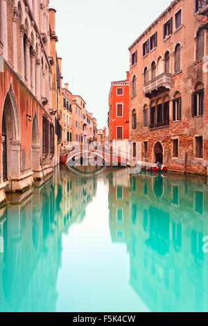 Water Canal and Bridge in Venice in a long exposure photography. Venetian buildings in its typical architecture - Stock Photo