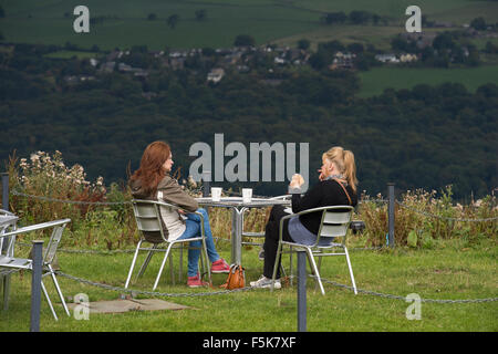 2 women friends sitting outside, eating & chatting at Cow & Calf Rocks café, Ilkley, Yorkshire, UK - scenic spot - Stock Photo