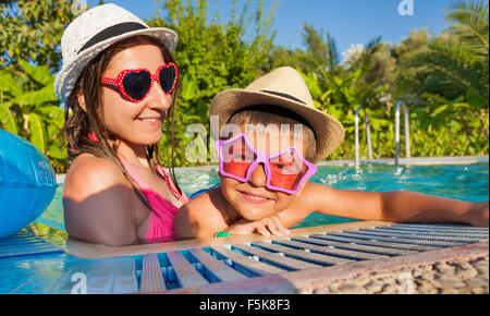 Happy woman and her son wearing sunglasses in pool - Stock Photo
