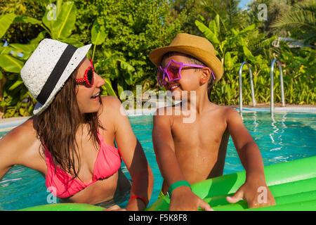 Happy mom and her son wearing sunglasses in pool - Stock Photo