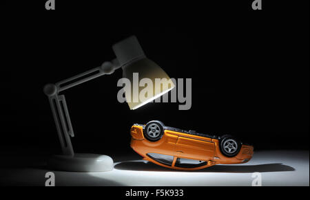 MODEL CAR UNDER SPOTLIGHT RE CAR INSURANCE ACCIDENT CLAIMS RISING MOTORING COSTS PRICES BUYING BUYERS CRASH SERVICING - Stock Photo