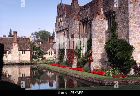 Exterior of a large, fortified country house with a moat and bright red salvias in a neat border - Stock Photo