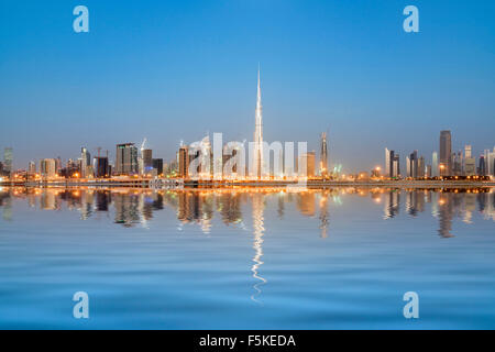 Skyline of towers reflected in the Creek at dawn in Business Bay  in Dubai United Arab Emirates - Stock Photo